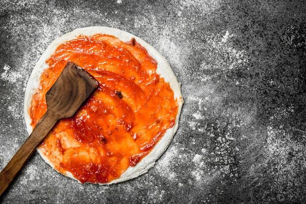 ピザの準備。丸めた生地にトマトソースをかけます。