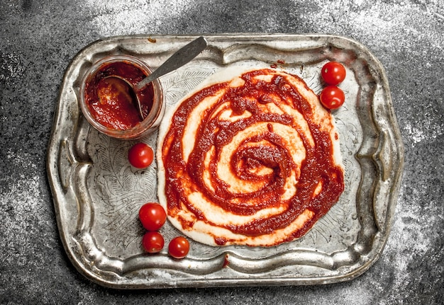 피자 준비. 압연 반죽에 토마토 소스를 바르십시오.