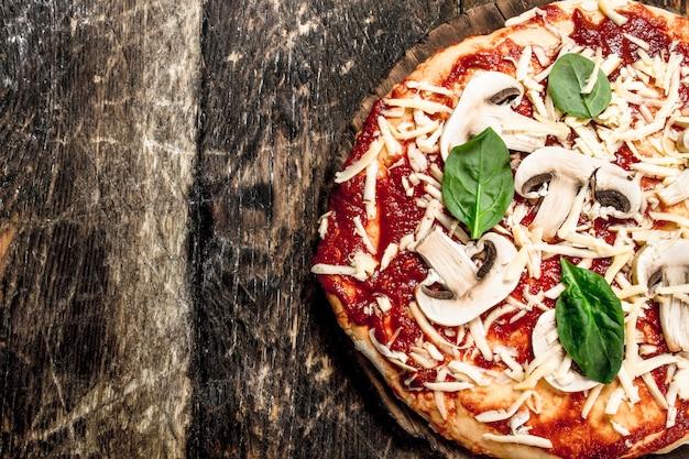 天然素材を使ったピザの作り方。木製の背景に。