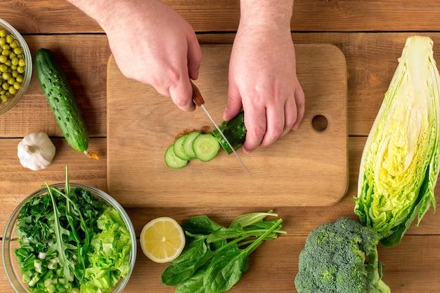 신선한 야채 샐러드 준비. 남성의 손에 커팅 보드에 칼으로 오이를 잘라.