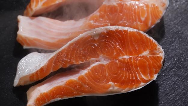 Приготовление стейка из лосося, приправленного солью и посыпанным сырым кусочком лосося
