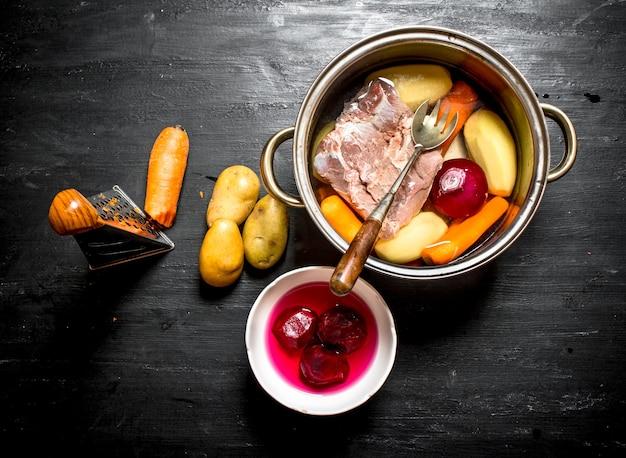 新鮮な野菜からのスープの準備。黒い木製の背景に。