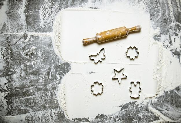 生地の準備。麺棒とクッキーの形をした小麦粉。石のテーブルの上。テキスト用の空き容量。上面図