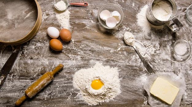 生地の準備。卵と他の材料で小麦粉。木製のテーブルの上。上面図