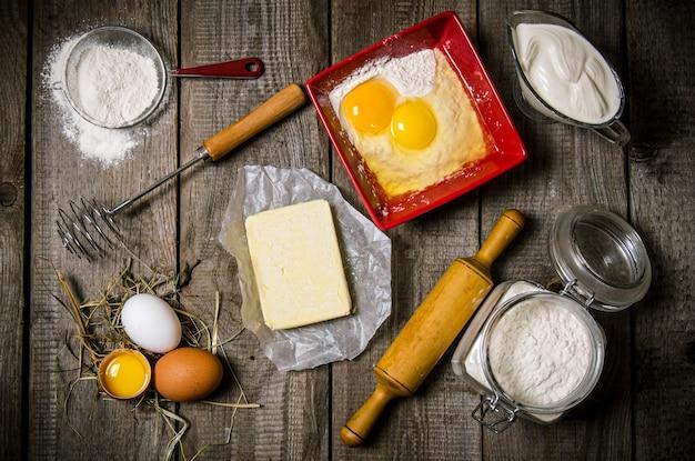 生地の準備。生地の材料-卵、小麦粉、バター、サワークリーム、麺棒で泡立て器。木製のテーブルの上。上面図