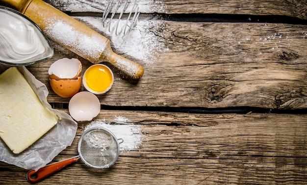 生地の準備。生地の材料-めん棒で卵、小麦粉、バター。木製のテーブルの上。テキスト用の空き容量。上面図