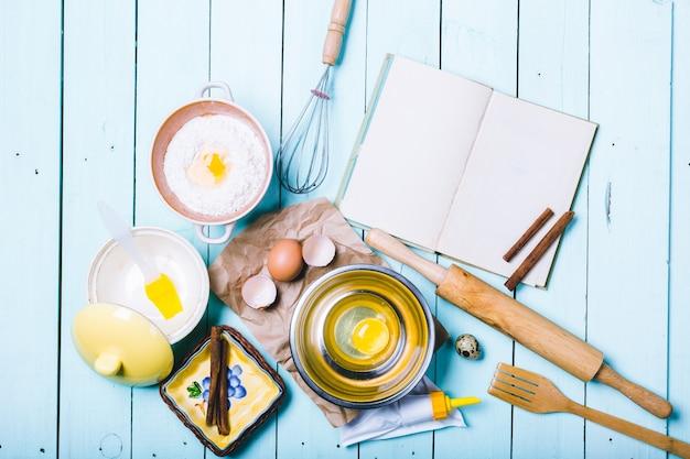 生地の準備。生地の材料-麺棒で卵と小麦粉。木製の背景に。