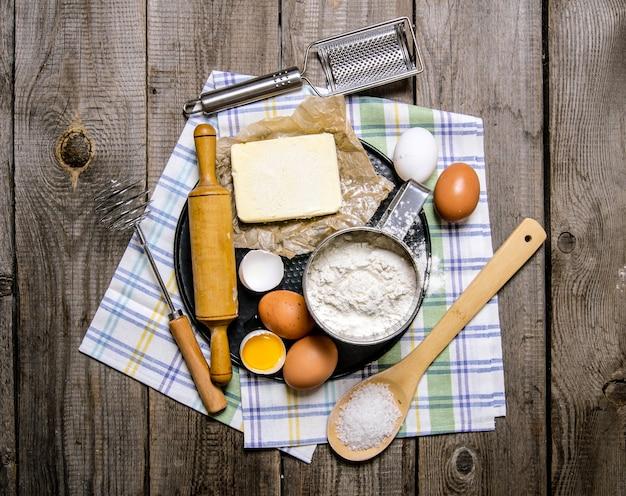 반죽 준비. 반죽 재료-계란, 버터, 밀가루, 소금 및 직물 도구. 나무 표면에. 평면도
