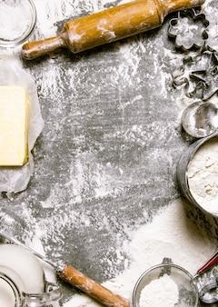 반죽 준비. 반죽 재료-밀가루, 버터, 우유 및 다양한 도구. 돌 테이블에. 텍스트를위한 여유 공간. 평면도