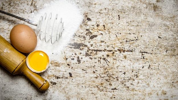 生地の準備。生地の材料-小麦粉、卵、めん棒。素朴な背景に。テキスト用の空き容量。上面図