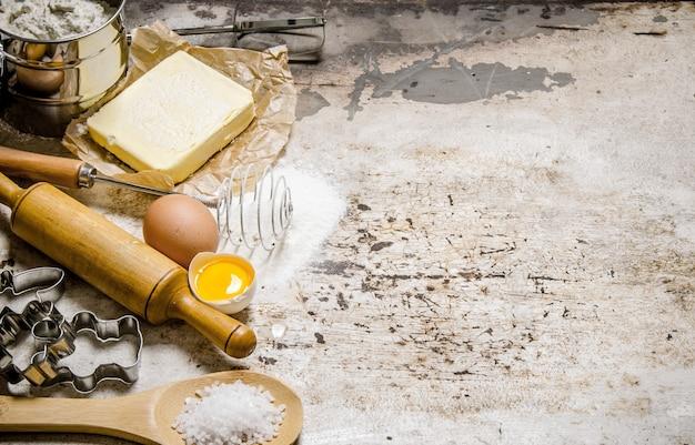 生地の準備。生地の材料-小麦粉、卵、バター、さまざまな道具。素朴な背景に。テキスト用の空き容量。上面図