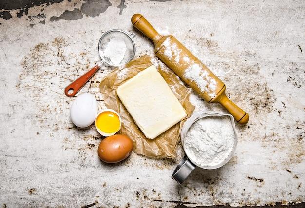 生地の準備。生地の材料-小麦粉、卵、麺棒付きバター。素朴な背景に。上面図