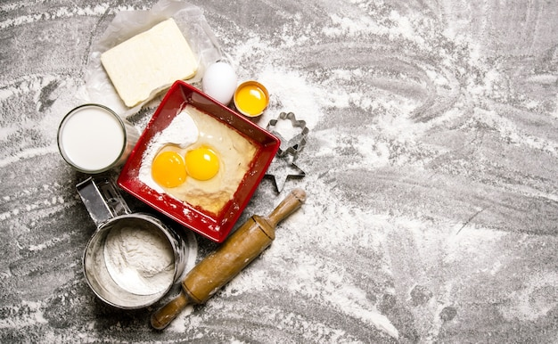 生地の準備。生地の材料-小麦粉、卵、牛乳、麺棒付きバター。石のテーブルの上。テキスト用の空き容量。上面図