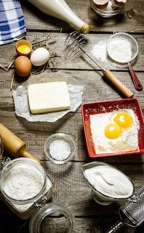 生地の準備。生地の材料-ミルク、クリーム、バター、小麦粉、塩、卵、さまざまな道具。木製のテーブルの上。上面図