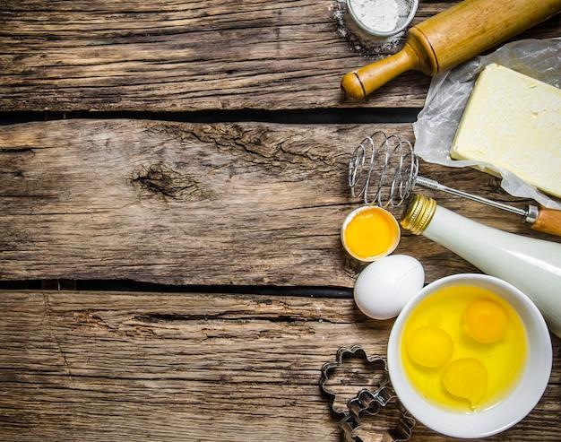 生地の準備。生地の材料-ミルク、卵、バター、小麦粉、泡立て器。木製のテーブルの上。テキスト用の空き容量。上面図