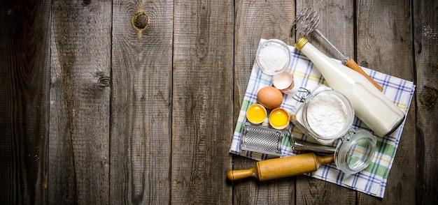 生地の準備。生地の材料-布にミルク、卵、小麦粉。木製のテーブルの上。テキスト用の空き容量。上面図