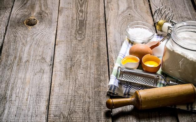 生地の準備。生地の材料-布にミルク、卵、小麦粉。木製のテーブルの上。テキスト用の空き容量。