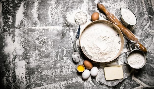生地の準備。生地の材料-小麦粉、サワークリーム、バター、めん棒で卵をふるいにかけます。