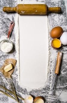 生地の準備。石のテーブルに小麦粉やその他の材料を入れた麺棒。テキスト用の空き容量。上面図