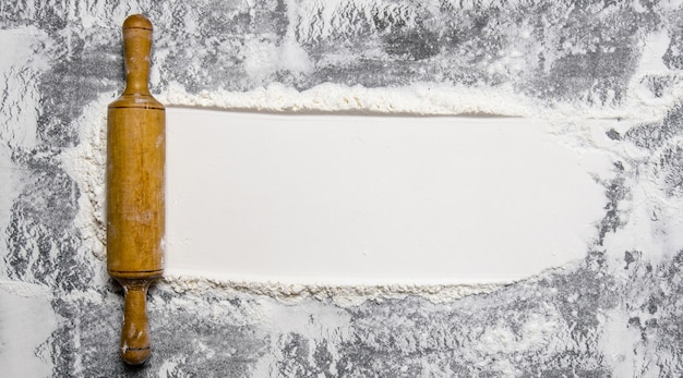 生地の準備。石の背景に小麦粉と麺棒。テキスト用の空き容量。上面図