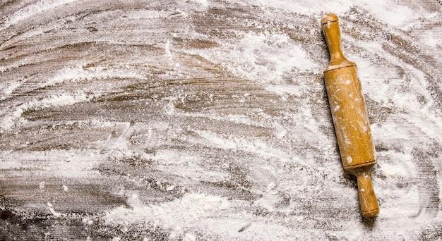 生地の準備。木製のテーブルに小麦粉と麺棒。テキスト用の空き容量。上面図