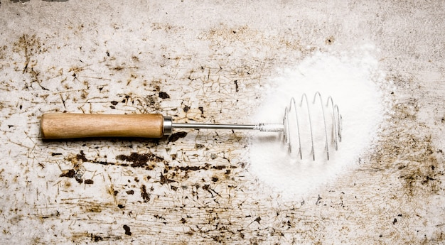 生地の準備。小麦粉で泡だて器。素朴な背景に。上面図