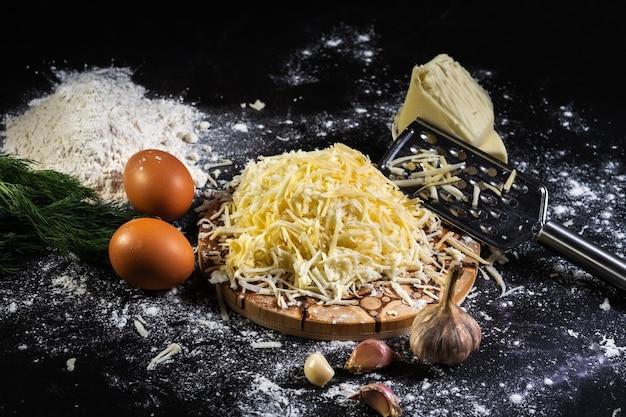 검은 배경에 마늘과 딜로 치즈 볼을 요리하는 과정 준비
