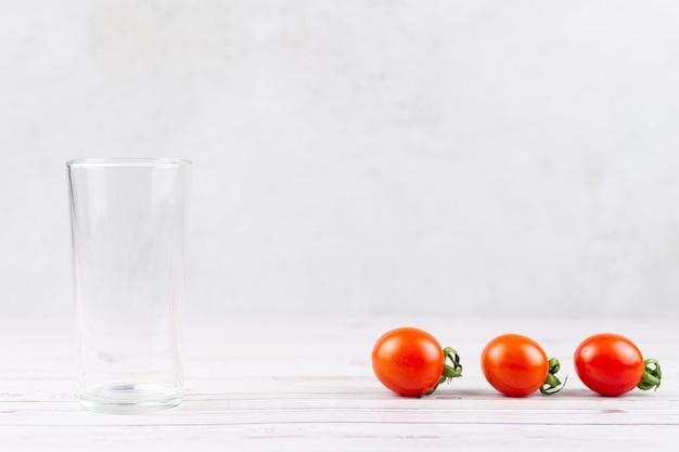 Приготовление томатного сока из спелых сочных свежих трех помидоров на серой поверхности