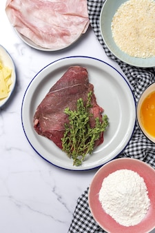 Приготовление традиционного домашнего эскалопа из телятины по-миланезе с мукой, яйцом, панировочными сухарями, сыром и ветчиной