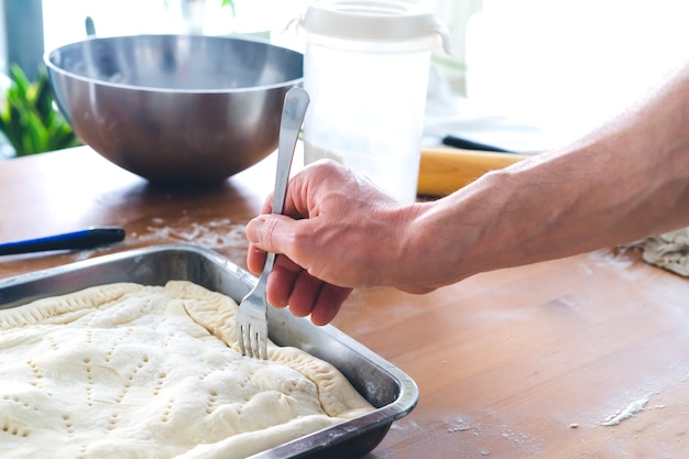 Preparation of patty for baking. kitchen concept. man's hand.