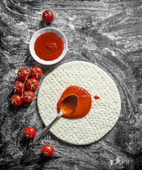 Приготовление пиццы. раскатанное тесто с томатной пастой и свежими помидорами. на деревенском фоне