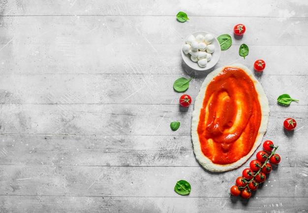Приготовление пиццы. раскатанное тесто с томатной пастой, моцареллой и шпинатом. на белом деревянном фоне