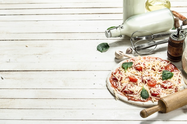 Preparation of pizza with various ingredients. on a white wooden table.