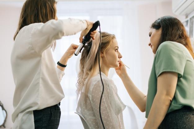 화려한 젊은 여성 미용사의 준비 과정이 긴 머리를 비틀고 있다