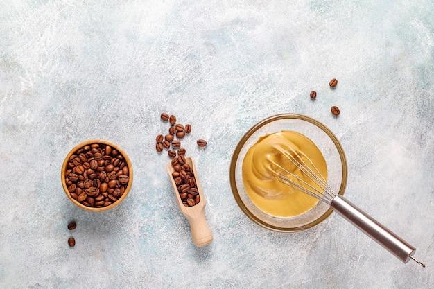 Процесс приготовления модного пушистого сливочного кофе далгона.