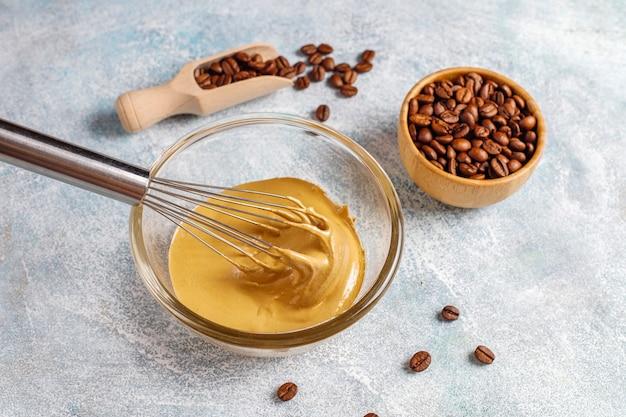 トレンディなフワフワのクリーミーなダルゴナコーヒーを準備します。