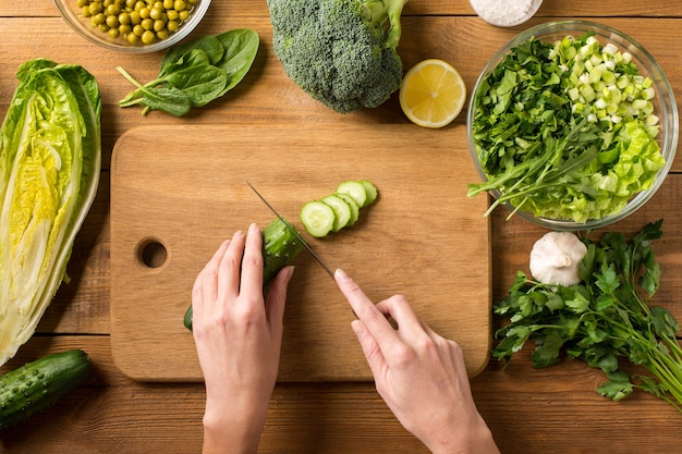 Preparation of salad from fresh vegetables. female hands cut the cucumber with a knife on a cutting board.