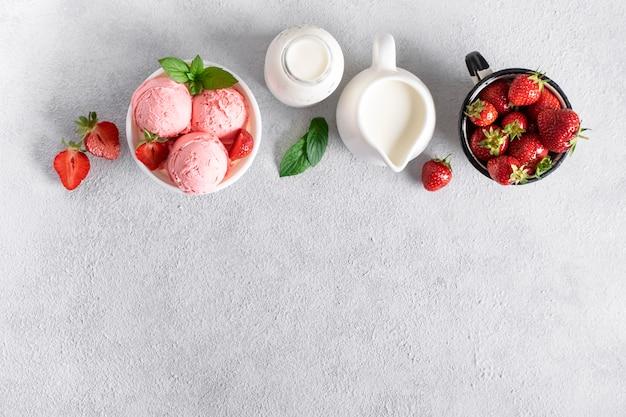 Приготовление клубничного мороженого. ингредиенты для приготовления мороженого. шар мороженого, сливк, клубник на конкретной предпосылке, взгляд сверху.