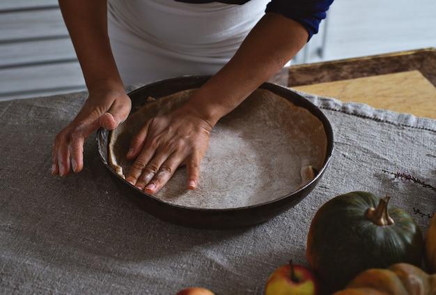 準備、感謝祭のお祝い。料理人が生地を鉄の型に入れます。彼女の手で生地を均一にします。テーブルの近くにはリンゴとカボチャがあります。