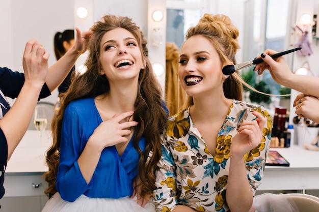 美容院での楽しい若い女性の素晴らしいパーティーへの準備