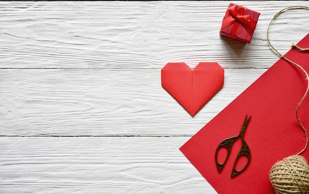 Preparation for valentine's day. red sheet of paper, scissors, red origami heart, skein of twine and gift box on a white wooden  handmade. st. valentine's day