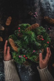 Preparation for xmas holidays. woman decorating christmas green wreath with pine cones and red winter berries, on dark rusty  , top view  copyspace, female hands