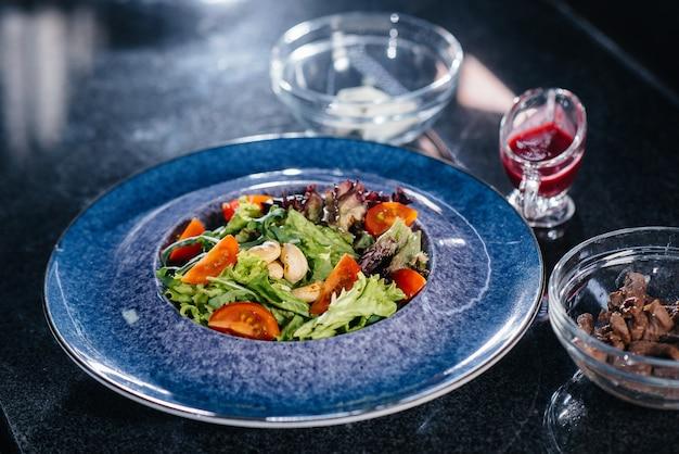 Приготовьте вкусный свежий салат из помидоров, зелени, сыра, телятины и орехов кешью. вкусная здоровая еда.