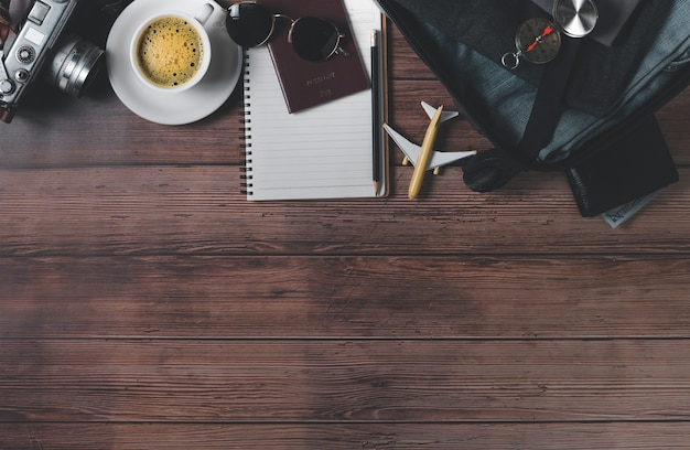Подготовьте чемодан, старинный фотоаппарат, блокнот, карту и черный кофе на деревянном полу и скопируйте место. концепция путешествия