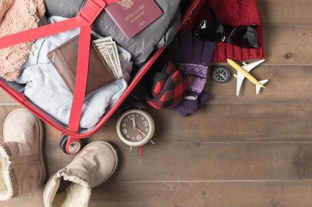古い木製ボード、フラットレイ、トップビューのバックグラウンドで冬の旅行のためのアクセサリーと旅行アイテムを準備する