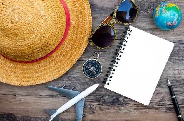 Подготовка аксессуаров и предметов для путешествия на деревянной доске, плоская планировка, вид сверху