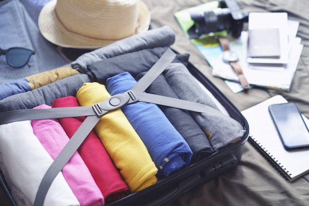 Prepare accessories for journey and travel to long weekend trip, packing clothes in suitcase bag on bed.