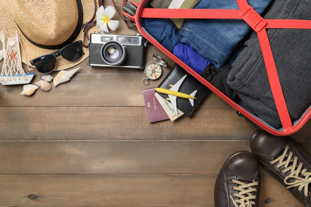 Prepare accessories and travel items with  baggage on wooden