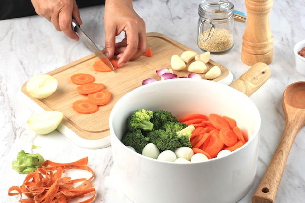 Prepare cooking slicing carrots above wooden chopping board female hand cooking vegtables
