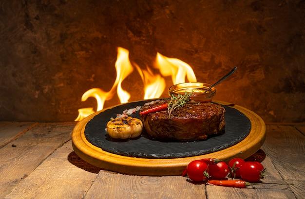 Приготовленный стейк из говядины на деревянном столе против огня